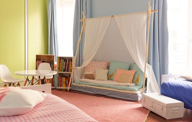 cameretta arredata con un divanetto sotto una tenda, una libreria e cuscini colorati